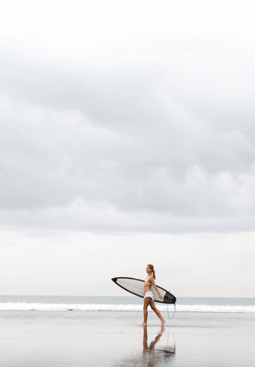 sober living houses pb surfer grey day sea woman shoreline blue sand walking